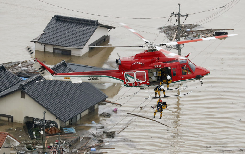 An aerial view shows a local resident being rescued from a submerged house by rescue workers using helicopter at a flooded area in Kurashiki, southern Japan, in this photo taken by Kyodo on July 7, 2018. Photo by Kyodo via Reuters