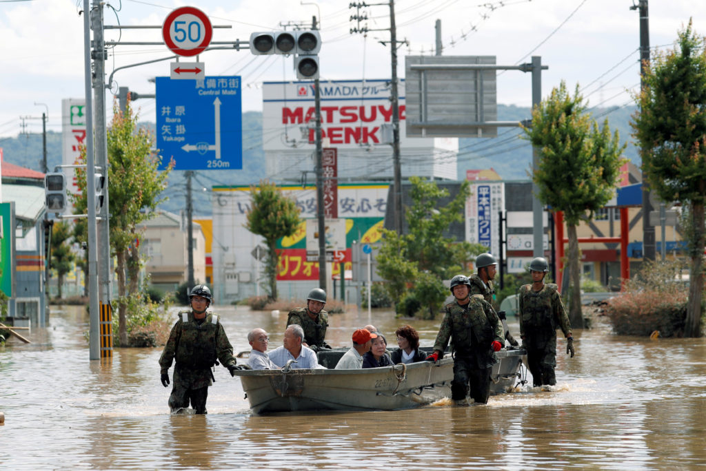 Japan Self-Defense Force soldiers rescue people from a flooded area in Mabi town in Kurashiki, Okayama Prefecture, Japan. Photo by Issei Kato/Reuters