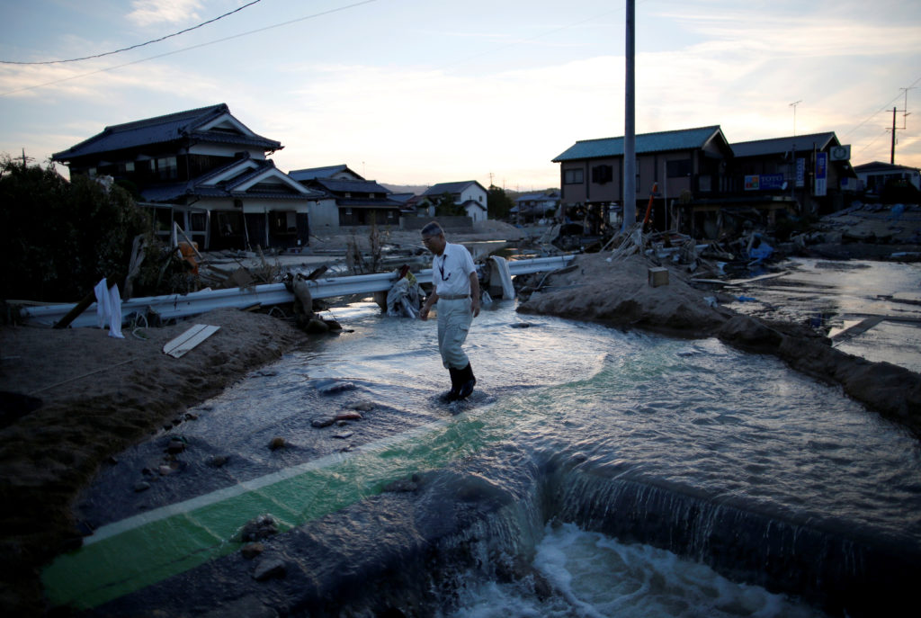 A local resident walks in a flooded area in Mabi town in Kurashiki, Okayama Prefecture, Japan. Photo by Issei Kato/Reuters