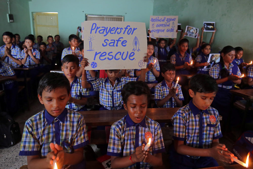 Schoolchildren pray for the schoolboys who are trapped inside a flooded cave in Thailand's northern province of Chiang Rai, at a school in Ahmedabad, India, on July 9. Photo by Amit Dave/Reuters