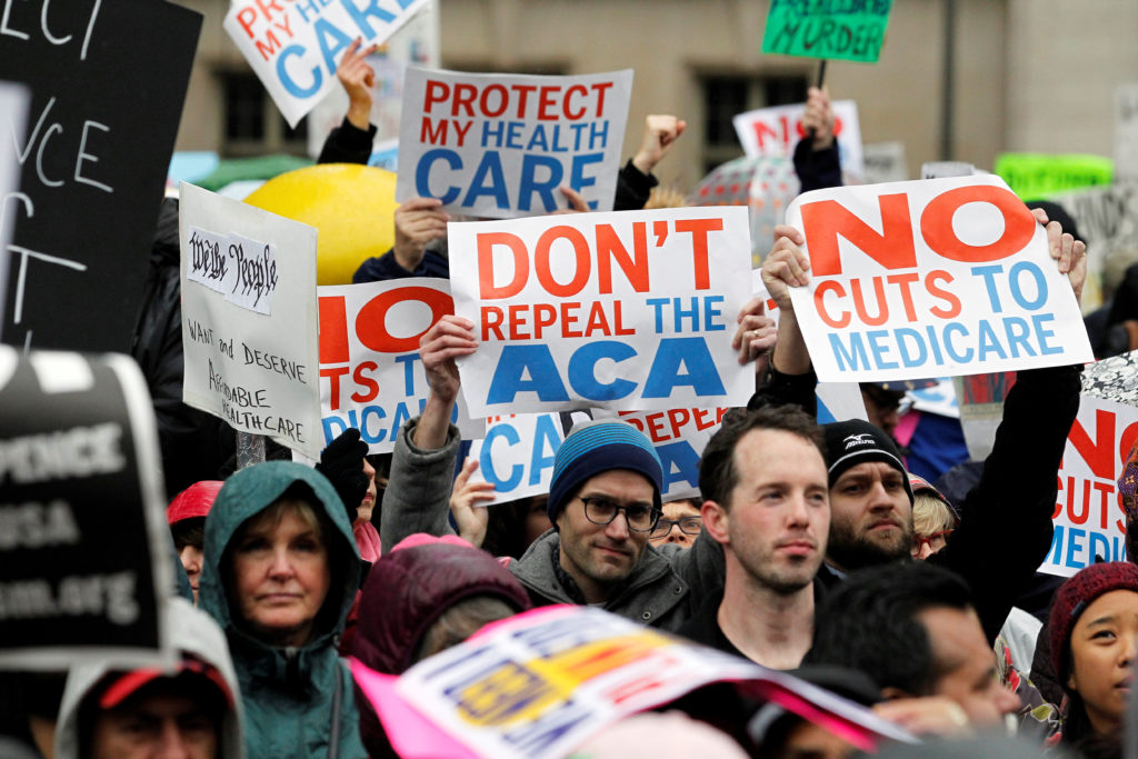 Demonstrators hold signs in support of the Affordable Care Act at a gathering before the start of a protest march near the...