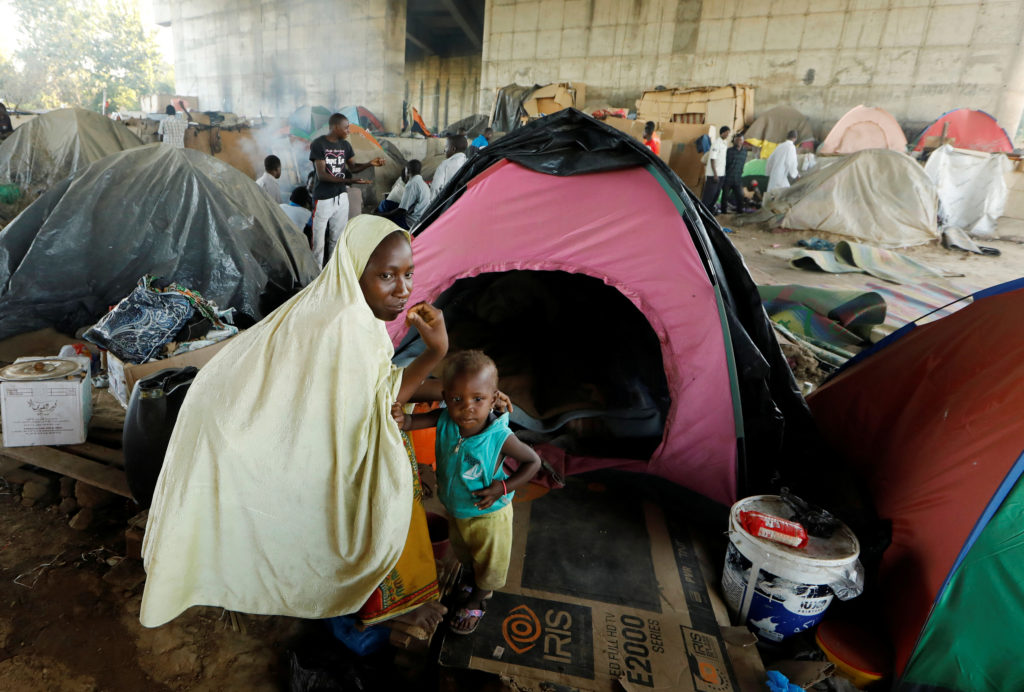 An African migrant and her son take shelter at a makeshift camp set up under a bridge on the outskirts of Algiers, Algeria on June 28. Photo by Zohra Bensemra/Reuters