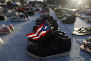 A Puerto Rican flag is seen on a pair of shoes as hundreds of pairs of shoes displayed at the Capitol to pay tribute to Hurricane Maria's victims after a research team led by Harvard University estimated that 4,645 people lost their lives, a number not confirmed by the government, in San Juan, Puerto Rico June 1, 2018. REUTERS/Alvin Baez - RC131BFE7FC0