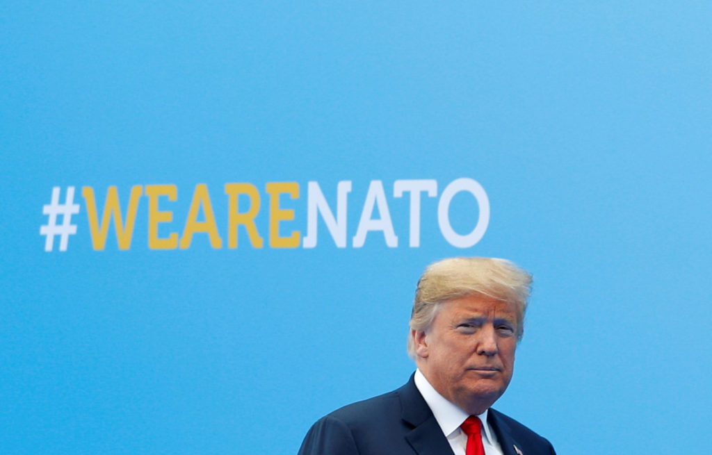 President Donald Trump walks at the start of a NATO summit at the A…