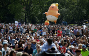 A blimp resembling U.S. President Donald Trump floats above demonstrators marching to protest against the visit of Trump, in Edinburgh, Scotland July 14, 2018. Photo by Andrew Yates/Reuters