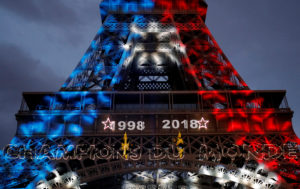 Blue, White, and Red lights and two World Cup stars are projected on the Eiffel Tower after France won the Soccer World Cup final. Photo by Philippe Wojazer/Reuters