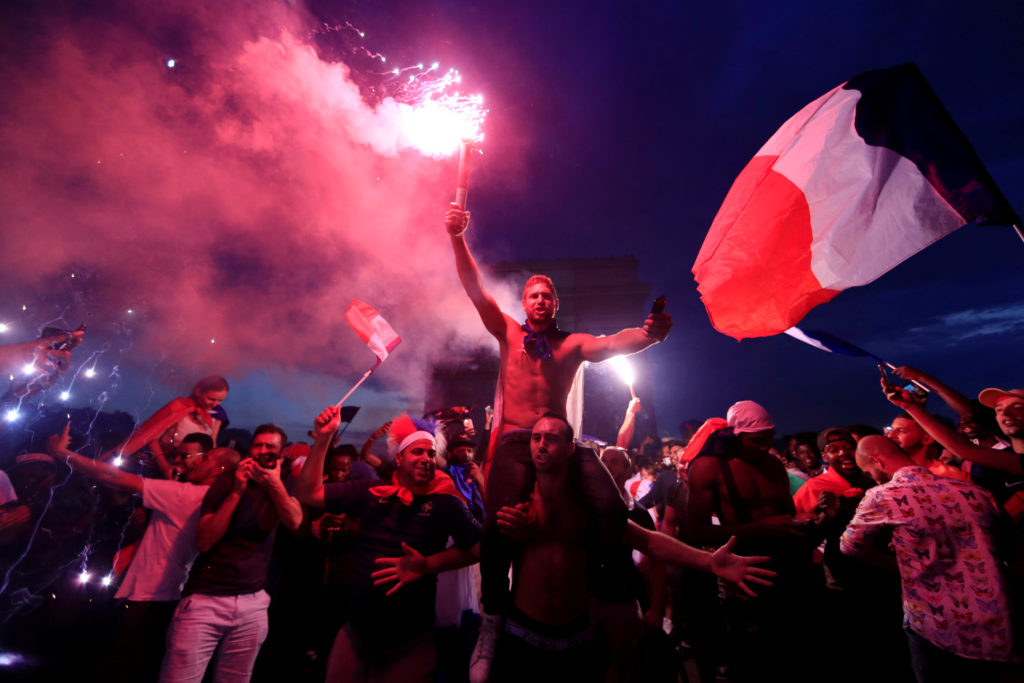 France fans celebrate in front of the Arc de Triomphe on the Champs-Elysees Avenue after France won the Soccer World Cup final. Photo by Gonzalo Fuentes/Reuters