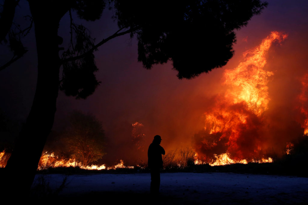 A man looks at the flames as a wildfire burns in the town of Rafina, near Athens, Greece. Photo by Costas Baltas/Reuters