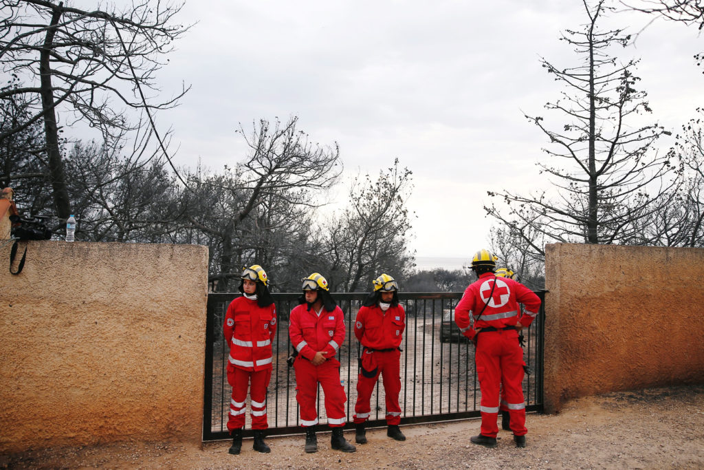 Rescue team members stand next to the area where bodies were found following a wildfire at the village of Mati, near Athens, Greece. Photo by Costas Baltas/Reuters