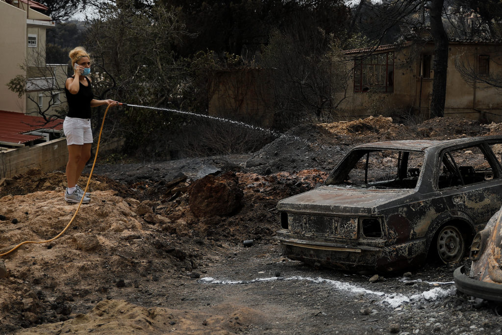 A local sprays water with a hose on a burnt car following a wildfire at the village of Mati, near Athens, Greece. Photo by Alkis Konstantinidis/Reuters