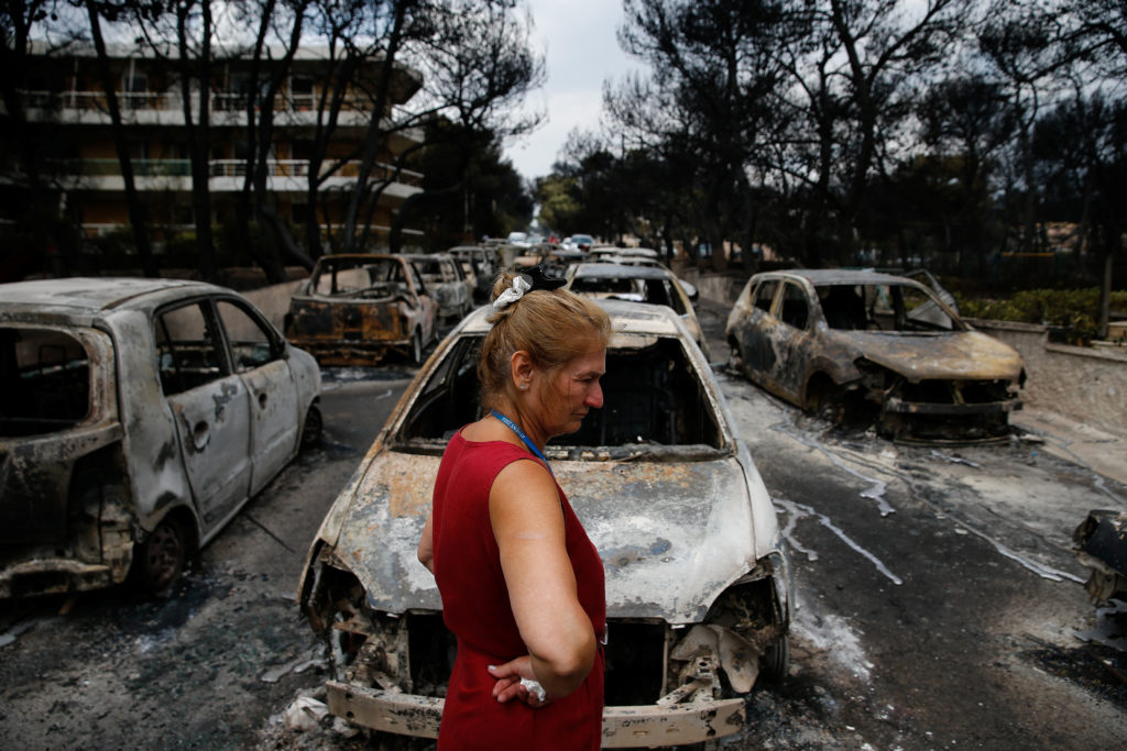 A local stands next to burnt cars following a wildfire at the village of Mati, near Athens, Greece, Photo by Costas Baltas/Reuters