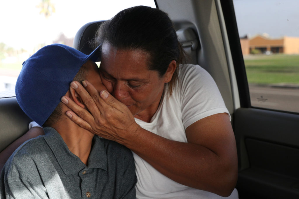 Maria Marroquin Perdomo and her 11-year-old son Abisai drive away from the Casa Padre facility in the backseat of her attorney's truck minutes after mother and son were reunified in Brownsville, Texas, on July 14, 2018. Abisai was held at Casa Padre while his mother was detained at the Port Isabel detention facility. Photo by Loren Elliott/Reuters