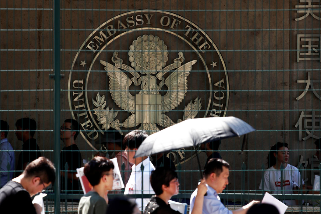 People wait outside the U.S. embassy, near the site of a blast in Beijing, China. Photo by Damir Sagolj/Reuters