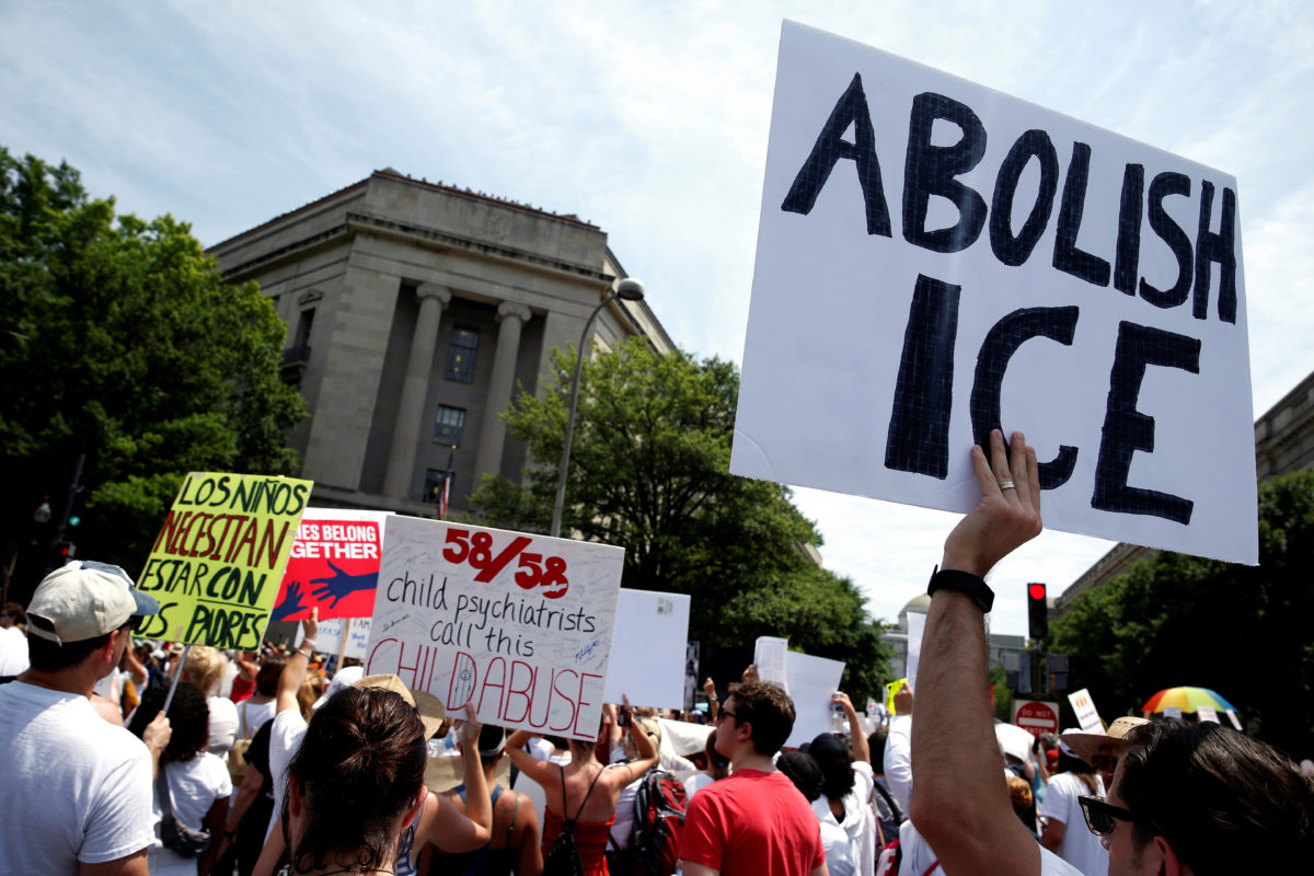 An immigration activist holds up a sign calling for the abolishment of ICE, U.S. Immigration and Customs Enforcement, during rally to protest the Trump Administration's immigration policy outside the Department of Justice in Washington, U.S., June 30, 2018. REUTERS/Joshua Roberts