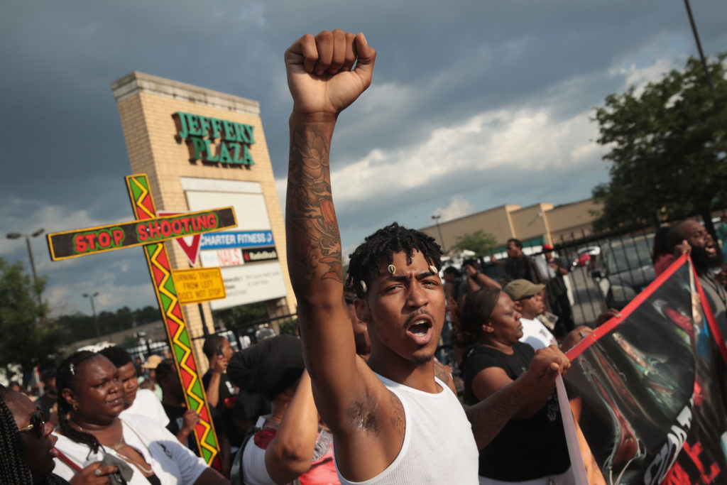 Demonstrators march through the South Shore neighborhood protesting the shooting death of 37-year-old Harith Augustus on July 15, 2018 in Chicago, Illinois. Augustus was shot by a Chicago Police officer yesterday following a brief altercation. Photo by Scott Olson/Getty Images