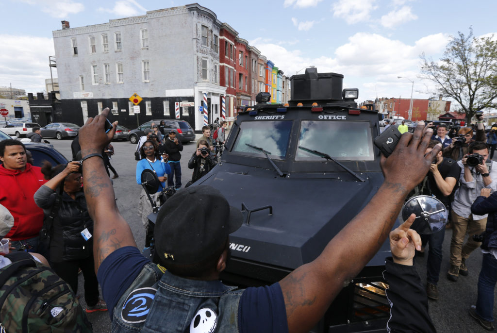 Members of the community try to force a police armored vehicle to reverse back down the street, near the site of a burned and looted CVS pharmacy, in Baltimore, Maryland, April 28, 2015. Photo by REUTERS/Jim Bourg