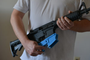 Travis Lerol holds an AR-15 assault rifle along with a rifle's lower receiver made of ABS (Acrylonitrile Butadiene Styrene) plastic that was constructed by his 3D printer at his home on Tuesday, February 12, 2012, in Glen Burnie, MD. Lerol is a techie and gun owner who has tried using a 3-D printing program that makes parts for the AR-15 style assault rifle. Photo by Jahi Chikwendiu/The Washington Post via Getty Images