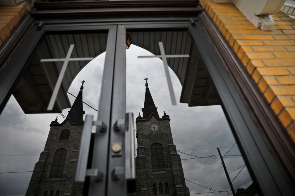 Divine Redeemer Catholic Church is reflected off another church across the street in Mt. Carmel, Pennsylvania. The church was one of the locations where a priest accused of sexual abuse had been assigned. Photo by Carlos Barria/Reuters