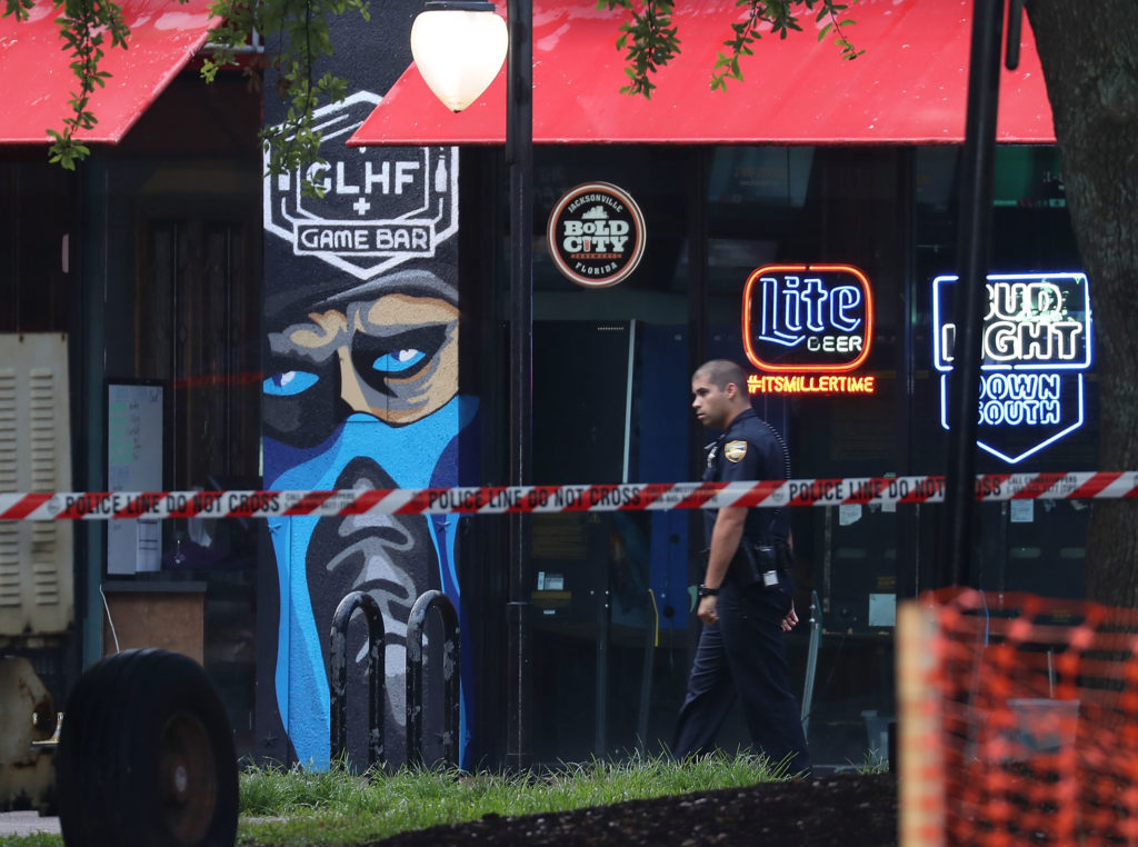 A Jacksonville, Florida, officer walks past the GLHF Game Bar where 3 people, including the gunman, were killed at the Jacksonville Landing on August 27, 2018 in Jacksonville, Florida. Photo by Joe Raedle/Getty Images
