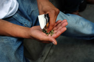 "A man prepares to smoke K2 or ""Spice"", a synthetic marijuana drug, along a street in East Harlem on August 5, 2015 in New York City. New York, along with other cities, is experiencing a deadly epidemic of synthetic marijuana usage including varieties known as K2 or ""Spice"" which can cause extreme reactions in some users. According to New York's health department, more than 120 people visited an emergency room in the city in just one week in April. While the state banned the ingredients used to make K2 in 2012, distributors have switched to other ingredients and names in an attempt to circumvent the law. (Photo by Spencer Platt/Getty Images)"
