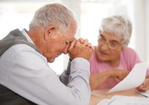 Two elderly people discussing a document