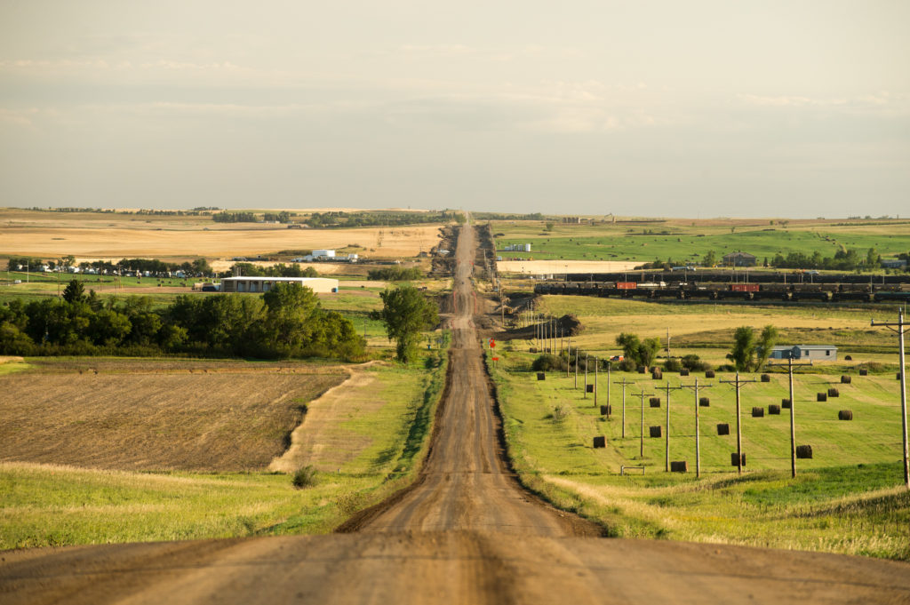 A view south on 93rd Ave., NW towards Hwy 2, a train hauling oil tank cars can be seen at right near Manitou, M.T., Sept 14, 2013. The train will soon be delivering crude oil to refineries in other parts of the state. Back in 2008 the North Dakota oil boom started its ongoing period of extraction of oil from the Bakken formation. The amount of jobs the oil boom has provided North Dakota has helped give it the lowest unemployment rate in the United States and and gave it a billion dollar surplus (Photo by Ken Cedeno/Corbis via Getty Images)
