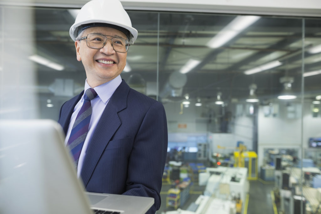 Senior businessman with hard hat at factory with laptop