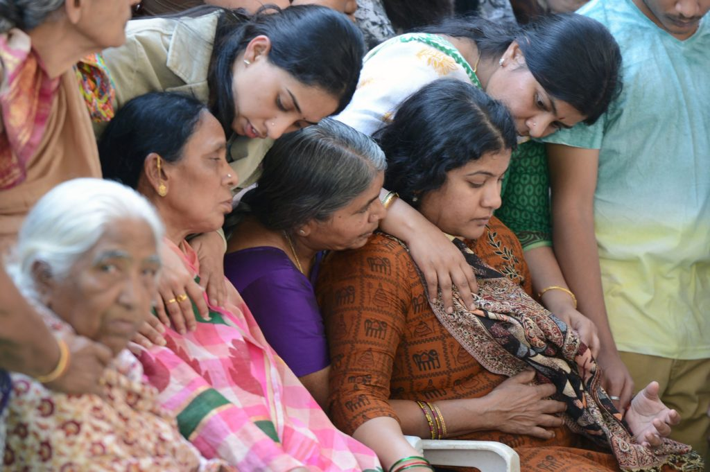 Sunayana Dumala (R), wife of killed Indian engineer Srinivas Kuchibhotla, who was shot dead in the US state of Kansas, is consoled by family members prior to performing the last rites at his funeral in Hyderabad, in February 2017. Photo by Noah Seelam/AFP/Getty Images
