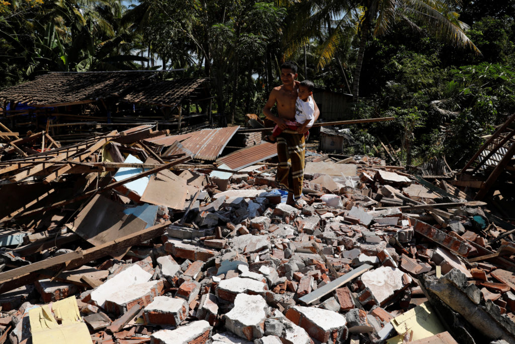 A man holds his child as he walks through the ruins of their house at Kayangan district after earthquake hit on Sunday in North Lombok, Indonesia, August 7, 2018. Photo by Beawiharta/Reuters.