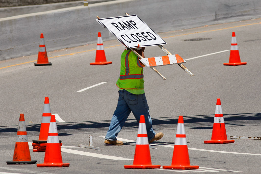 A worker removes road barriers from an onramp as the 405 freeway reopens after the demolition of the Mulholland Drive bridge in Los Angeles, California July 17, 2011. Photo by David McNew/Reuters