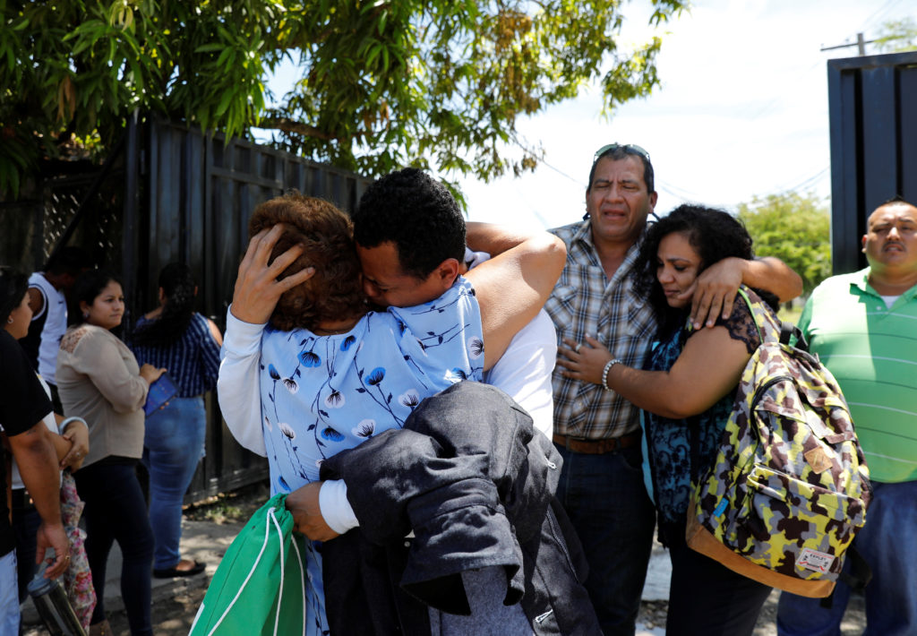 A Honduras deportee from the U.S., embraces a relative as he arrives with others, outside the Migrant Center San Pedro Sula, Honduras, in June. Photo by Carlos Jasso/Reuters