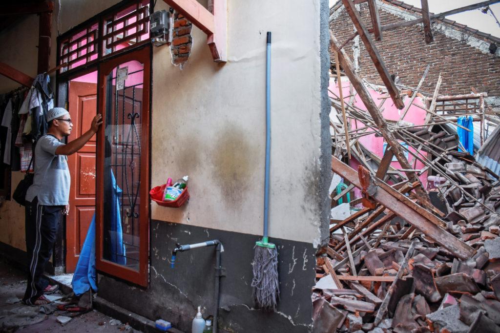 A man looks at his partially collapsed home. Photo by Antara Foto/Ahmad Subaidi via Reuters