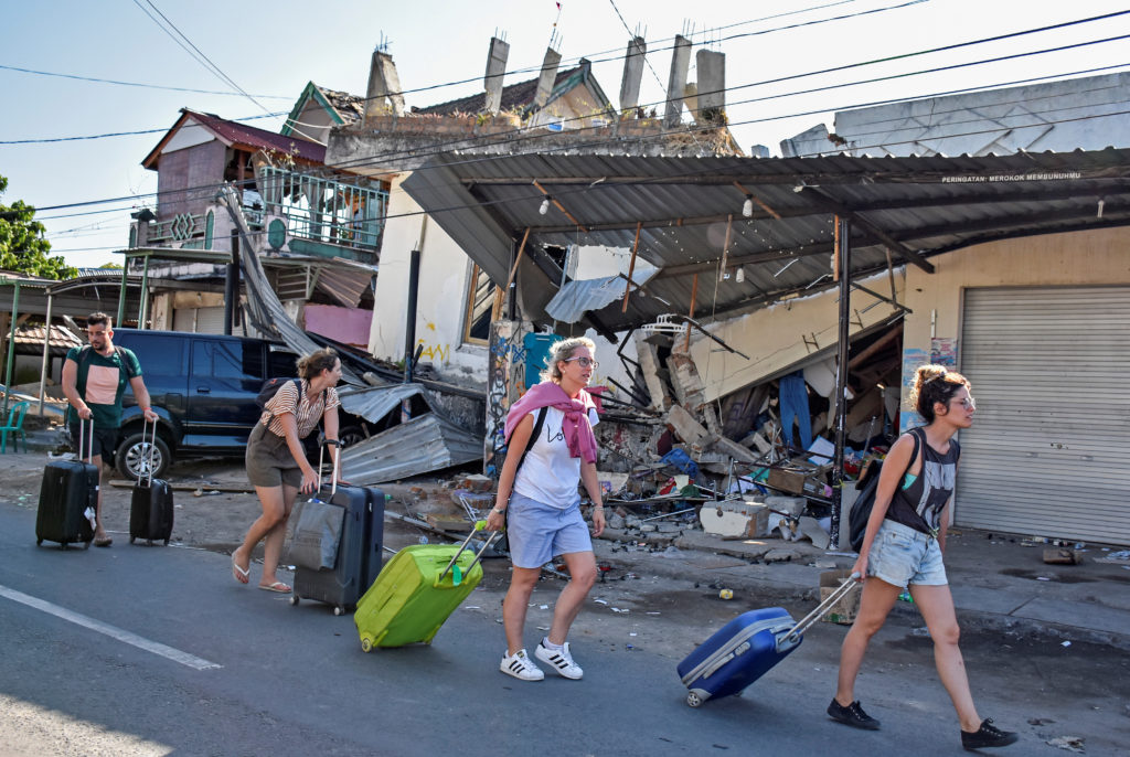Foreign tourists depart the islands on Aug. 6 following a major earthquake in Pemenang, North Lombok, Indonesia. Photo by Antara Foto/Ahmad Subaidi via Reuters