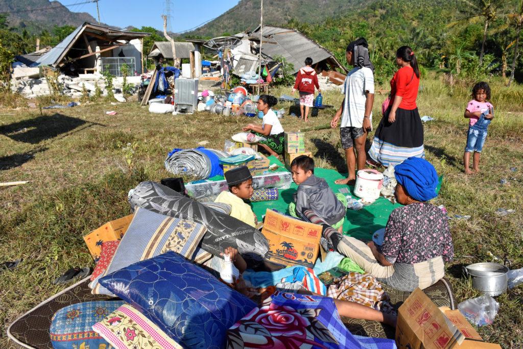 Residents sit outside their home with their belongings. Photo by Antara Foto/Ahmad Subaidi via Reuters