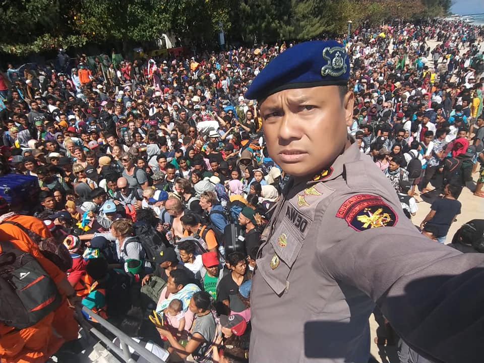 Chief Water Police of Lombok Dewa Wijaya takes a picture in front of hundreds of people attempting to leave the Gili Islands in Lombok after the earthquake struck. Photo by Indonesia Water Police/Handout/via Reuters