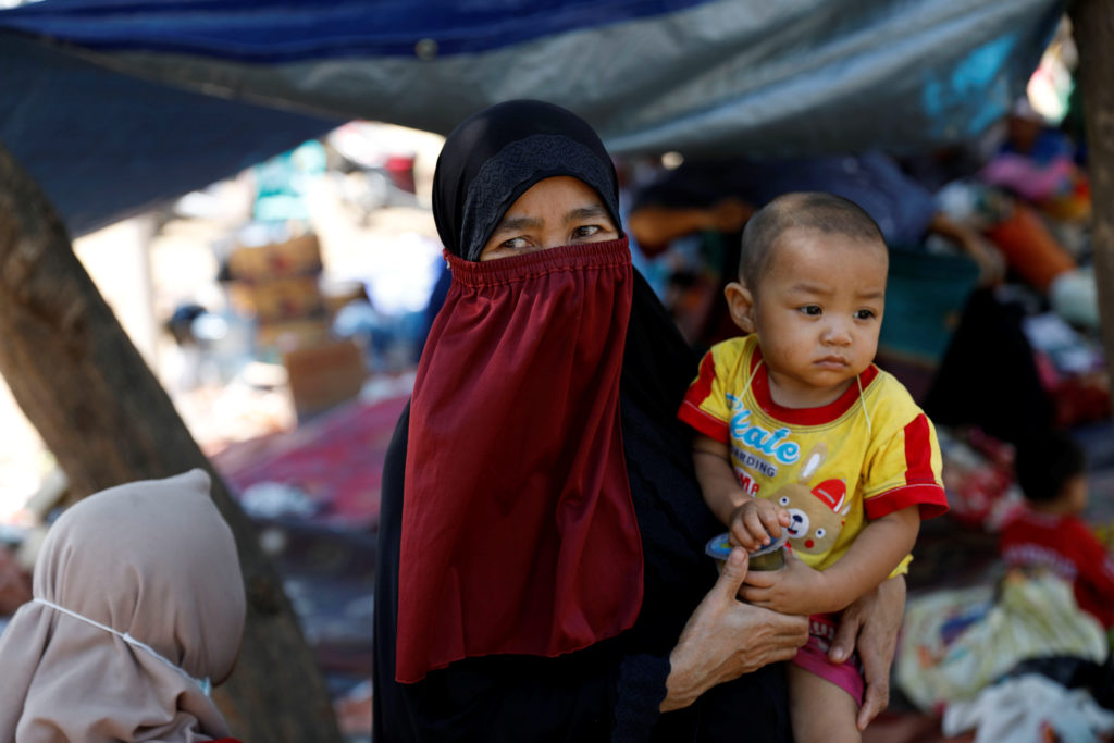 A villager holds her child at a temporary shelter on Aug. 6 after an earthquake hit Lombok island in Indonesia. Photo by B...