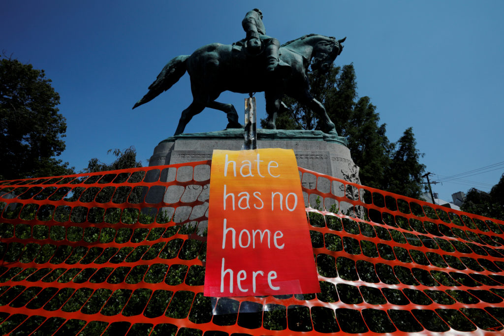 """A sign reading """"Hate Has No Home Here"""" hangs by the statue of Civil War Confederate General Robert E. Lee in Charlottesvil..."""