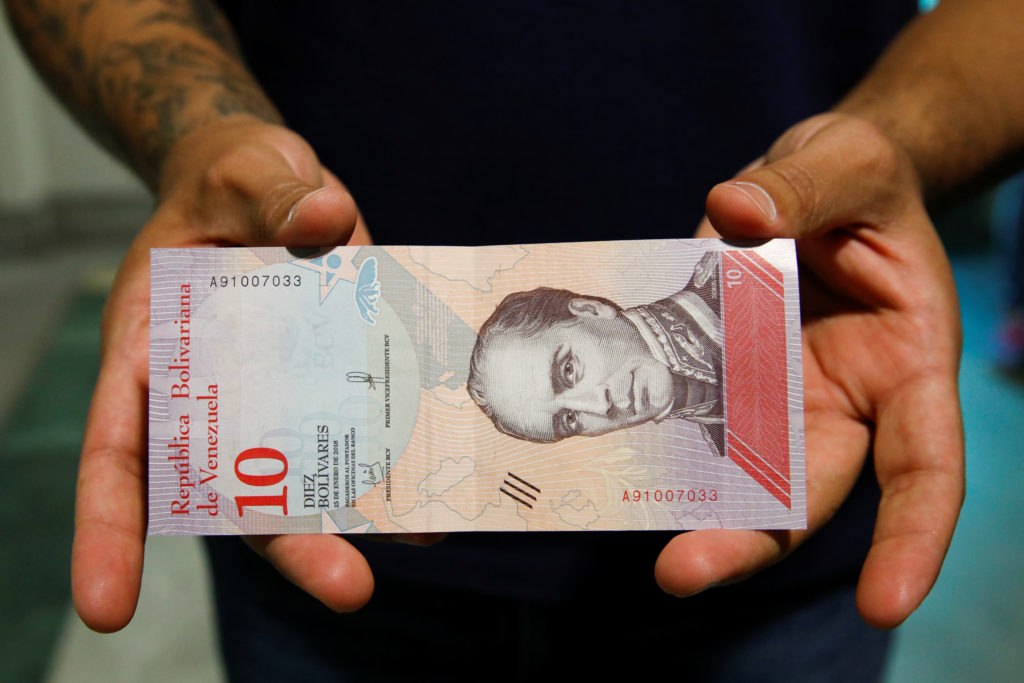 A man shows a new sovereign bolivar bill in Caracas, Venezuela on Aug. 20. Photo by Carlos Garcia Rawlins/Reuters