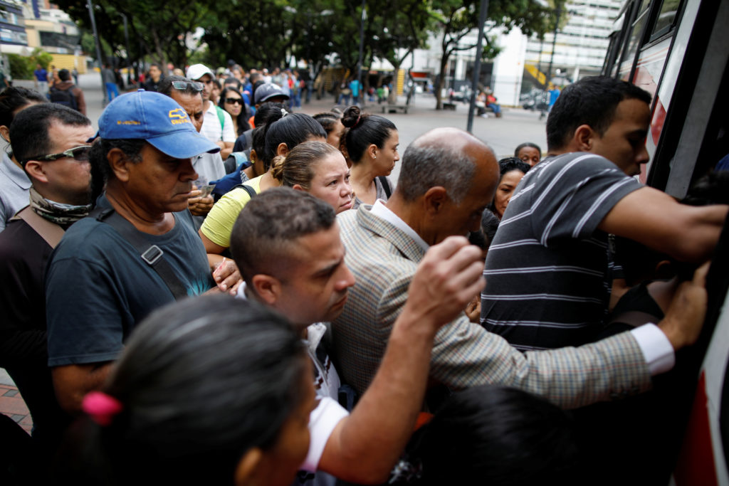 People line up for a bus to leave Caracas. Photo by Carlos Garcia Rawlins/Reuters
