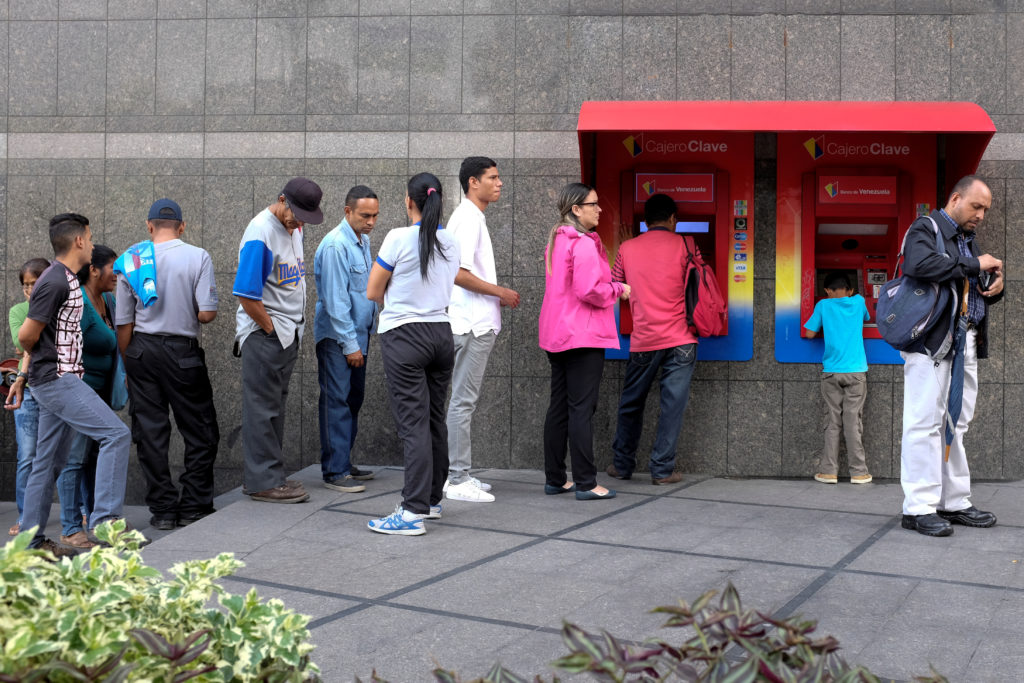People withdraw cash from automated teller machines. Photo by Marco Bello/Reuters