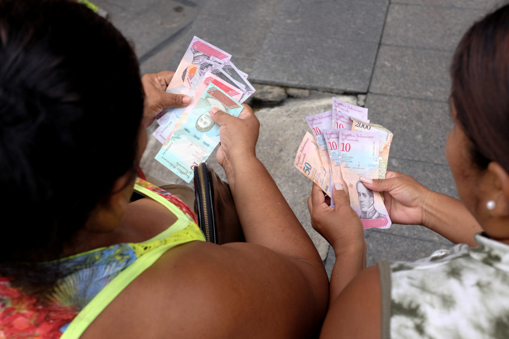 Women count their money in Caracas. Photo by Marco Bello/Reuters