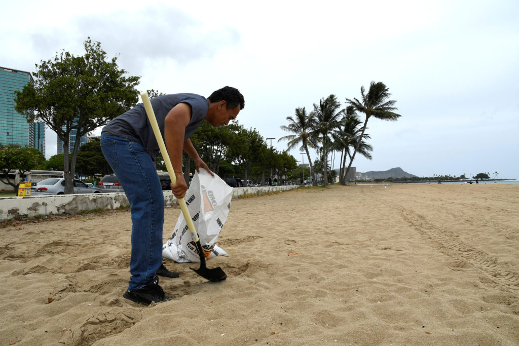 Mike Gonsalves gathers sand from a beach to fill sand bags as Hurricane Lane approaches Honolulu, Hawaii. Photo by Hugh Gentry /Reuters