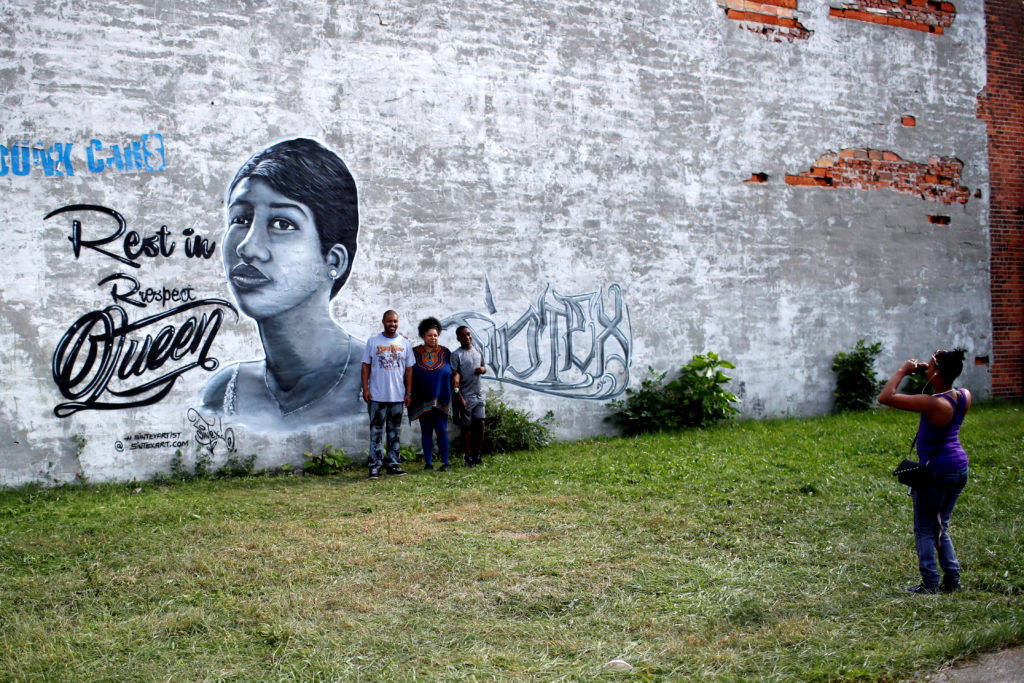 A family is photographed beneath a mural in tribute to the late singer Aretha Franklin outside the New Bethel Baptist Church in Detroit, Michigan. Photo by Mike Segar/Reuters