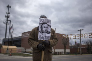 A man demanding the criminal indictment of the white police officer who shot dead unarmed black teenager Michael Brown in August, holds an image of Brown outside the Ferguson Police Station in Missouri, November 24, 2014. REUTERS/Adrees Latif/Files - GF20000010173
