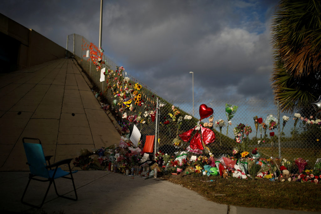 An empty chair is seen in front of flowers and mementos placed on a fence to commemorate the victims of the mass shooting at Marjory Stoneman Douglas High School, in Parkland, Florida. Photo by Carlos Garcia Rawlins/Reuters