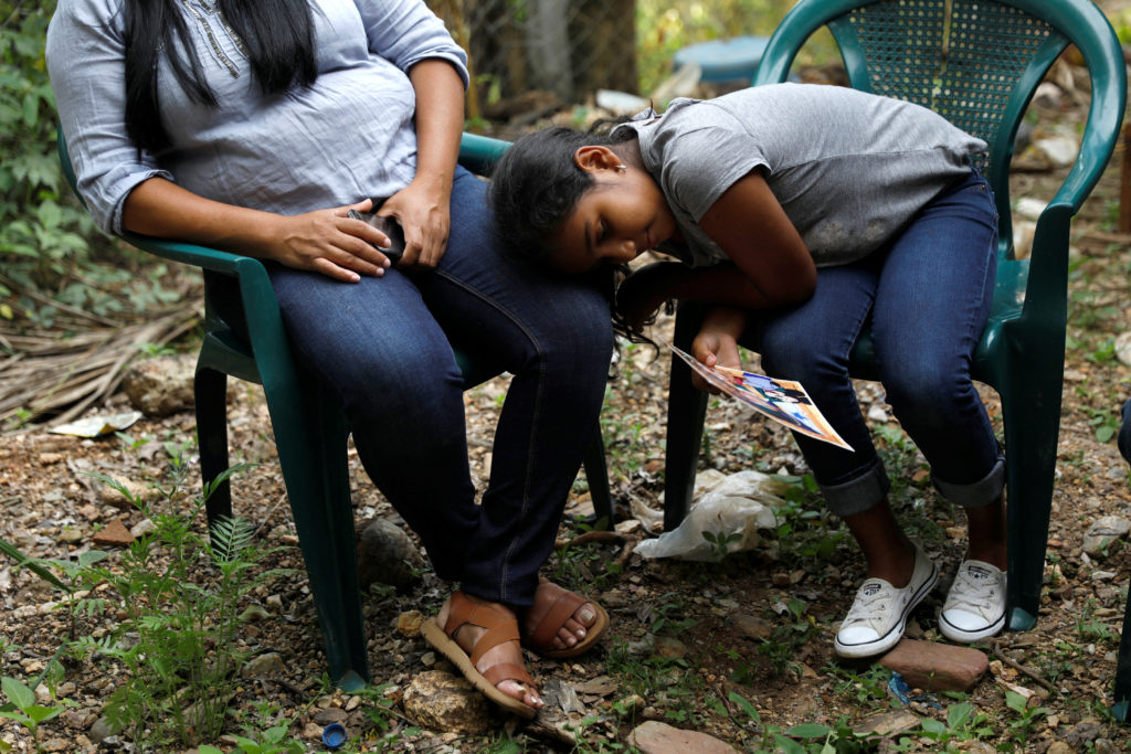 Marcela, 9, daughter of Douglas Almendarez, 37, a deportee from the U.S. who was separated from his son Eduardo Almendarez, 11, at the Rio Grande entry point under the Trump administration's hardline immigration policy, rests on her mother's leg, in La Union, in Olancho state Honduras July 14, 2018. Photo by Edgard Garrido/Reuters