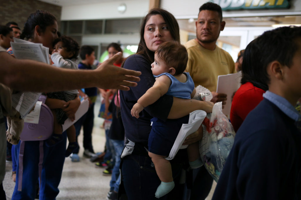An undocumented immigrant mother and her infant son are released from detention with other families at a bus depot in McAl...