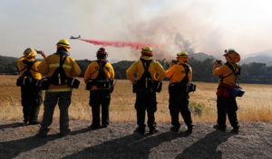 Firefighters watch as an air tanker drops fire retardant to protect homes along the crest of a hill at the River Fire (Mendocino Complex) near Lakeport, California, on August 2, 2018. Photo by Fred Greaves/Reuters