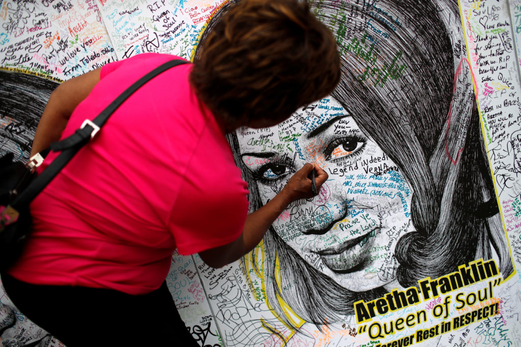 A woman writes on a large drawing of Aretha Franklin outside the Charles H. Wright Museum of African American History on the second day of a public viewing of the late singer in Detroit, Michigan, U.S., August 29, 2018. REUTERS/Mike Segar