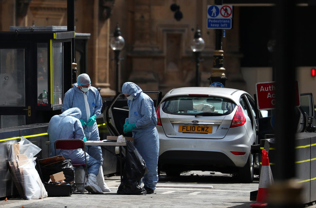 Forensic investigators work at the site after a car crashed outside the Houses of Parliament in Westminster, London, Britain, August 14, 2018. REUTERS/Hannah McKay